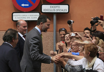 Spanish Crown Prince Felipe greets people during his visit to an exhibition in the Andalusian capital of Seville