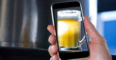 Hand taking picture of beer glass through smart phone at bar