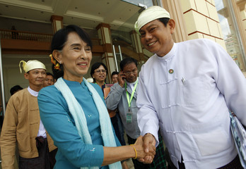 Myanmar pro-democracy leader Suu Kyi shakes hands with Htay Oo, Secretary-General of the Union Solidarity and Development Party, after attending a meeting at the Lower House of Parliament in Naypyitaw