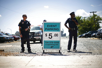 Members of law enforcement stand in a parking lot during the Coalition to March on Wall Street South protest in Charlotte