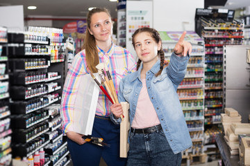 Mother and daughter standing among art supplies