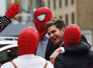 Actor Andrew Garfield messes around with friends dressed in Spider Man masks at the world premiere of The Amazing Spiderman 2 in central London
