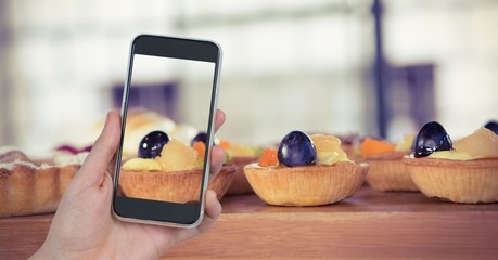 Hand taking picture of tart through smart phone