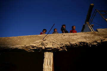Children play on the roof of a damaged house in the rebel held besieged town of Douma, eastern Ghouta in Damascus