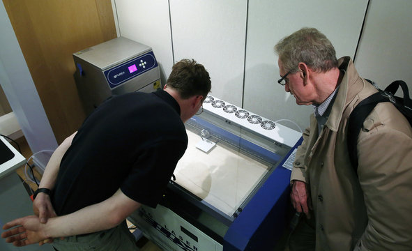 TechShop rep Leoni demonstrates laser cutter during media preview for GE Garages in Washington