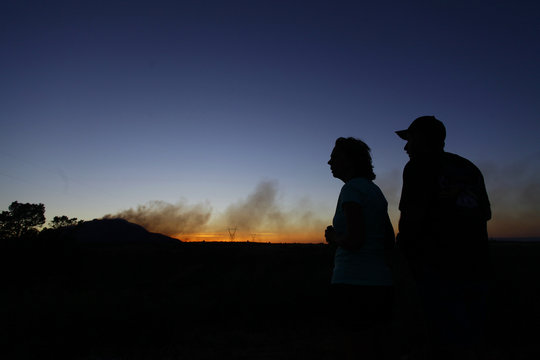 Kim Clements and Jerry Clements are silhouetted as they watch smoke rise from the Doce Fire in Yavapai County
