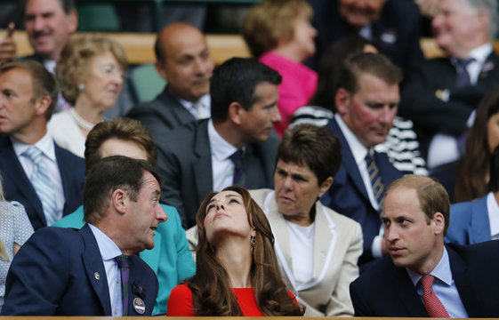 Britain's Catherine Duchess of Cambridge looks up to the sky during a rain delay as Prince William (R) talks on Centre Court at the Wimbledon Tennis Championships in London