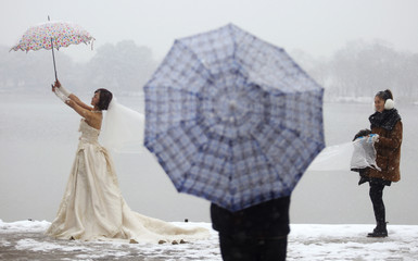 A woman wearing a wedding dress poses for pictures in snow next to the West Lake of Hangzhou