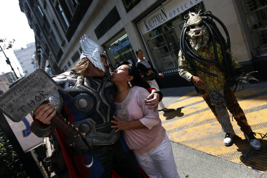 Street artist Ruben Oviedo, dressed as comics superhero Thor, pretends to kiss a woman during a performance in downtown Mexico