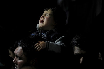 A baby cries during a protest by stranded refugees at the Greek-Macedonian border who wait for the border crossing to reopen near the Greek village of Idomeni