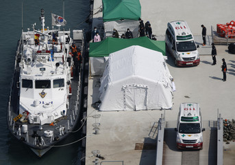 An ambulance carrying the body of a passenger who was on the capsized passenger ship Sewol which sank in the sea off Jindo, leaves at a port in Jindo