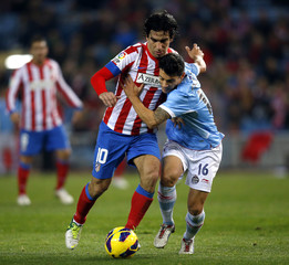 Atletico Madrid's Arda Turan fights for the ball with Celta Vigo's Carlos Bellvis Llorens during their Spanish first division soccer match at Vicente Calderon stadium in Madrid