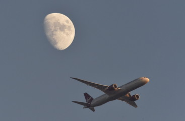 A Virgin Atlantic passenger plane flies in the sky with the moon seen in the background, in London, Britain