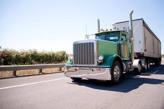 Big rig attractive green semi truck with bulk trailer