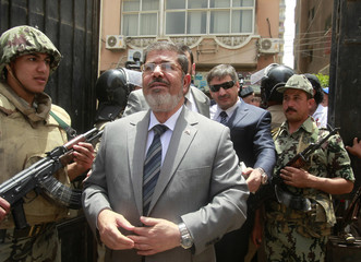 Islamic presidential candidate Mohamed Mursi arrives to a polling station to cast his vote in Al-Sharqya