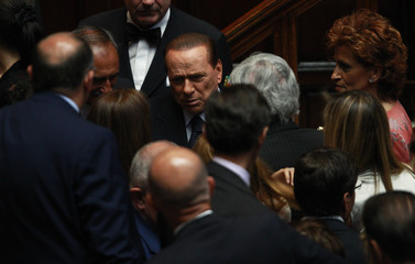 Italian Prime Minister Silvio Berlusconi talks with members of the lower house of parliament during a debate in Rome