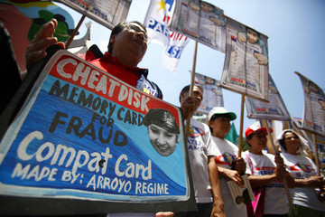 People hold a mock-up of the compact flash card used in the automated voting system in Manila