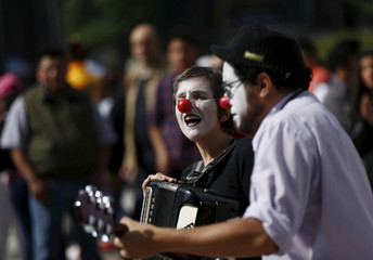 Street musicians with their face painted as clowns, play the accordion and a guitar as pedestrians look on in Mexico City