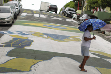 A woman uses an umbrella with a soccer ball design as she crosses Jonathas Pedrosa street in Manaus