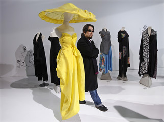 A visitor walks past a yellow strapless silk dress and oversized coolie hat covered with draped silk designed by Yohji Yamamoto at the V&A in London