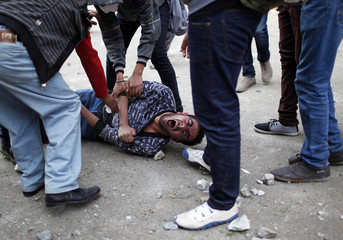 Anti-Mursi protesters try to carry a man affected by tear gas during clashes with riot police at Tahrir Square in Cairo