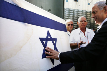 Israeli Prime Minister Netanyahu touches the original flag Israeli paratroopers waved at the Western Wall during the 1967 Middle East War, before a special cabinet meeting in Jerusalem