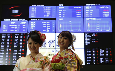 Women, dressed in ceremonial kimonos, pose for photos in front of an electronic board showing Japan's stock price index after the New Year opening ceremony at the TSE in Tokyo