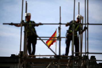 Workers build a pipe structure on a scaffolding during the World Day for Safety and Health at Work in the Andalusian capital of Seville