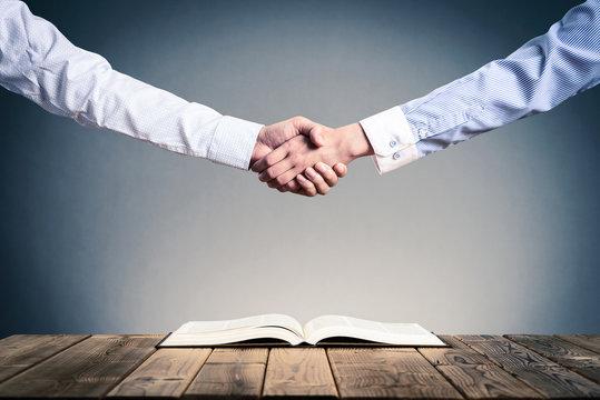 開いて置いてある本,ビジネスマンの握手