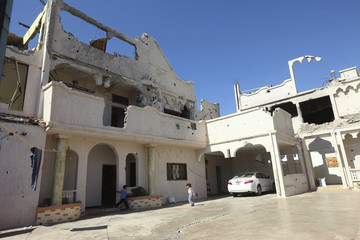 Children run in the courtyard of a house, damaged during last year's war, in the Libyan town of Sirte