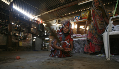 Ben, an earthquake survivor cleans her temporary tin tent, at Anjar town in the western Indian state of Gujarat