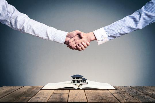 本の上に置かれた住宅模型,ビジネスマンの握手