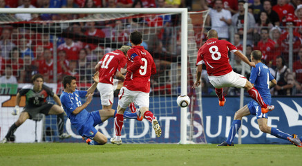 Switzerland's Gokhan Inler scores the first goal against Italy during their friendly soccer match in Geneva
