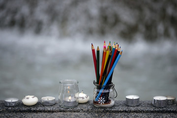 Pencils are seen near candles as several thousand people gather to pay tribute to the victims following a shooting by gunmen at the offices of the satirical weekly newspaper Charlie Hebdo during a demonstration in Nantes