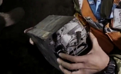 Rescue crew member holds the black box during the rescue operation at a remote crash site where a plane carrying 47 people crashed into a northern Pakistan mountain, in this still frame taken from video