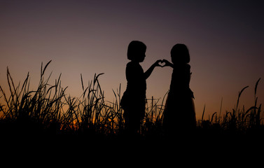 silhouette of Asian little girl standing on a grass field background of gorgeous sunsets. The girl shows love symbol with hand sign language.