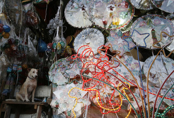A dog sits beside Christmas decorations displayed along a busy street in Manila