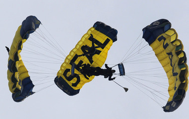 Members of the Navy Leap Frogs converge as they parachute into the stadium before the start the Army versus Navy NCAA football game in Philadelphia