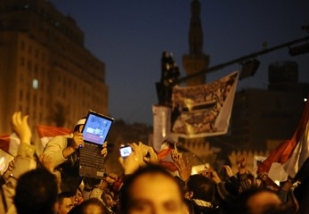 File photo of an opposition supporter holding up a laptop showing images of celebrations in Cairo's Tahrir Square, after Egypt's President Hosni Mubarak resigned