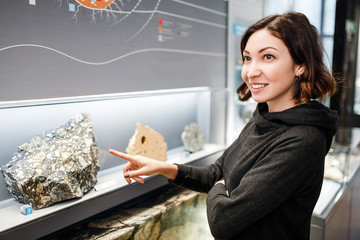 Beautiful Asian happy geologist woman indoors looking at minerals collection, education and science concept