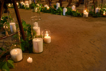many candles in glass vases on the floor on hipster style wedding ceremony