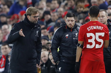 Liverpool's Kevin Stewart receives medical attention after sustaining an injury as manager Juergen Klopp looks on