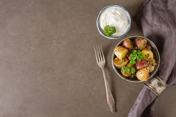 Body multicolored potato baked with herbs and garlic on olive oil, Dark background. Food for a vegan and a vegetarian.