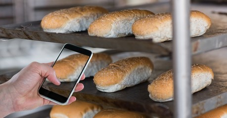 Hand taking picture of breads through smart phone at bakery