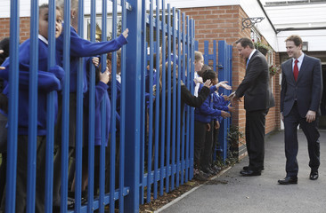 Britain's Prime Minister David Cameron (2nd R) and Deputy Prime Minister Nick Clegg arrive for a joint visit to Wellbeck Primary School in Nottingham, in central England