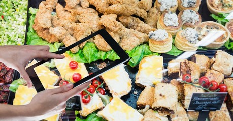 Hands taking picture of food through digital tablet
