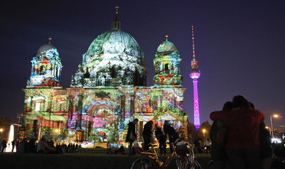 People watch as the Berlin cathedral and the television tower are illuminated during the Festival of Lights in Berlin