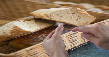 Cropped hands taking picture of bread