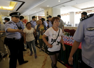 Relatives of missing firefighters are guided by policemen outside the venue of a news conference in Tianjin