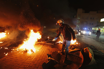 A riot police officer removes burning tyres from the highway set up by anti-government protesters in Diraz